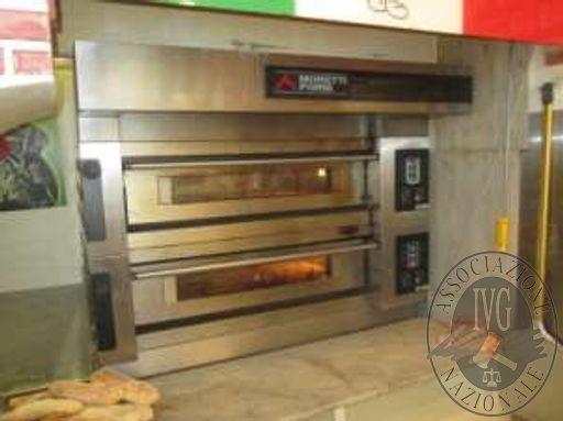 Un forno per pizza, una macchina per condizionamento d'aria ed un frigorifero in acciaio inox a due ante