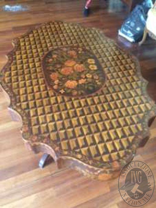 Un tavolo in legno con piano sagomato con intarsi e superficie in vetro