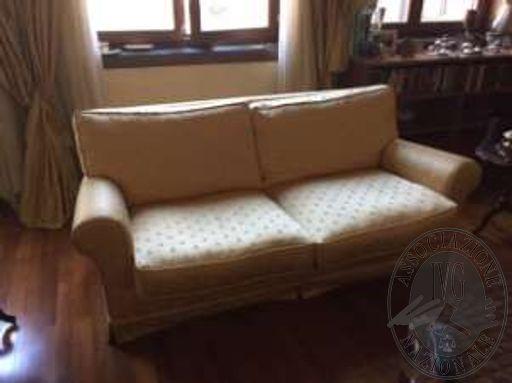 Un divano in tessuto di colore beige a due posti