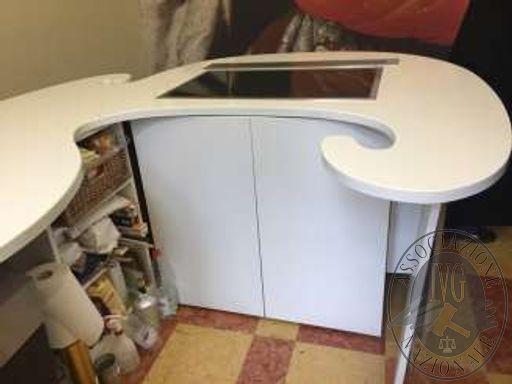 Bancone cucina con top di forma irregolare curvilea in quarzo di colore bianco, provvisto di lavello ad incasso, piano cottura Gaggenau e cappa d'aspirazione verticale a scomparsa.